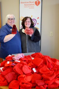 Care Connection Lifestyles Specialist Vickie Whitsitt (left) and Natalie Cronkhite, Coordinator of the Heart and Stroke Walk for the Kansas City-area American Heart Association, show off the caps for newborns.